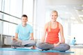 Meditating in gym portrait of healthy girl and guy doing exercise for relaxation Stock Photo