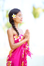 Meditating spiritual woman in meditation on beach vacation natural serene beauty relaxing zen moment wearing pink sarong and Stock Photos