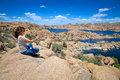 Meditating at watson lake a woman on a rock overlooking scenic prescott arizona Royalty Free Stock Images
