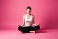 Meditating young woman in yoga position studio shot pink background Royalty Free Stock Image