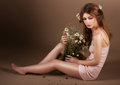 Meditation barefoot genuine woman with bouquet of flowers modest young wildflowers sitting in studio Stock Photography