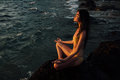 Meditation girl lotus position on stone on the background of the stunning sea. Royalty Free Stock Photo