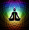Meditation in matrix silhouette of a man lotus position with seven chakras on rainbow colored energy background Royalty Free Stock Image