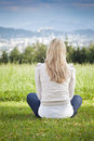 Meditation rear view of a woman with long blond her sitting on the grass overlooking a distant town enjoying the tranquillity Royalty Free Stock Photography