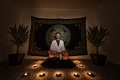 Meditation ritual a man sitting on a zafu cushion with in a white robe with his eyes closed doing a there are plants candles and a Royalty Free Stock Images
