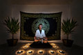 Meditation ritual a man sitting on a zafu with in a white robe staring intensely into the camera with his eyes open doing a there Royalty Free Stock Photos