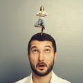 Meditation woman standing on the head small women of amazed man Stock Image
