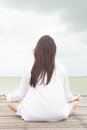 Meditation by young women woman in white dress on a bridge the sea Royalty Free Stock Photo