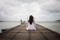 Meditation by young women woman in white dress on a bridge the sea Royalty Free Stock Image