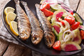 Mediterranean cuisine: grilled sardines with fresh vegetable sal