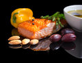 Mediterranean omega diet fish steak olives nuts and herbs on black background with reflection Royalty Free Stock Photos