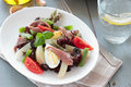 Mediterranean salad with anchovies and olives on the white plate Stock Photography
