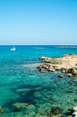 Mediterranean seashore of cyprus island with rocky coast and white yacht Stock Image