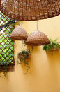 Mediterranean terrace design wicker lamps light wickerwork willow and green plants on yellow wall background Royalty Free Stock Photo