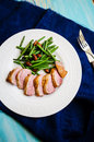 Medium rare duck breast with crispy skin young green beans and almond garnish Royalty Free Stock Photos