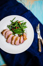 Medium rare duck breast with crispy skin young green beans and almond garnish Stock Photos
