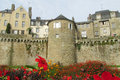 Medival castle walls behind the red flowers and tower in vannes france fortificated wall and tower among houses and in garden Stock Image