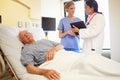 Medizinischer team meeting as senior man schläft im krankenhauszimmer Stockfotos
