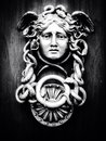 Medusa face on wooden door Stock Photo