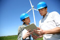Meeting in energy park engineers looking at wind turbine site with tablet Stock Photography