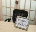 Meeting in progress sign front of closed doors Stock Image