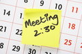 Meeting reminder written on yellow adhesive note paper and stuck to a wall calendar Stock Images
