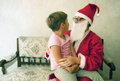 Meeting santa short haired little girl in s lap happy to meet him Stock Photo
