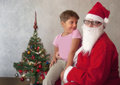 Meeting santa short haired little girl in s lap happy to meet him Stock Photography