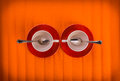 Meeting- two white empty cups with tea spoons, on red plates over orange color background, view from above Royalty Free Stock Photo