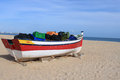 Meia praia lagos algarve portugal fishing boat with crates sits docked in the sands by the blue surt of in europe Stock Photo