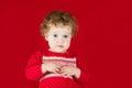 Meisje in een warme gebreide sweater op rode achtergrond Royalty-vrije Stock Foto's