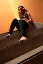 Melancholic stairway a young woman listening to music sitting in the Royalty Free Stock Photography