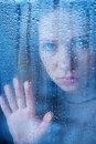 Melancholy and sad young woman at the window in the rain hand of Royalty Free Stock Photo