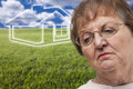 Melancholy senior woman and grass field and ghoste with green ghosted house behind her Royalty Free Stock Image