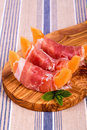 Melon and ham starters parma sliced starter served on olive wood board over striped tablecoth Royalty Free Stock Photos