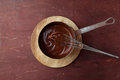 Melted chocolate swirl in pan with whisk on the wooden background Royalty Free Stock Photo