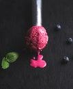 Melting blueberry ice-cream scoop over black slate stone background Royalty Free Stock Photo