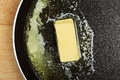 Melting butter piece of while in frying pan Royalty Free Stock Image