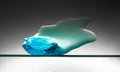 Melting piece of blue ice on glass sheet Royalty Free Stock Photography