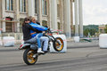 Member from stuntmen team rides motorcycle moscow jun avtorodeo togliatti trick with two women during speedfest at olympic complex Stock Photos