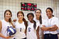 Members of female high school volleyball team with coach in gymnasium smiling Stock Photo