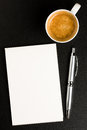 Memo book pen and coffee silver blank white notebook cup of over black background viewed from above will be useful for filling the Stock Photo