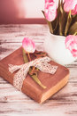 Memo still life with book key vintage lace and pink tulips Stock Photos