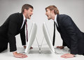 Men� confrontation two angry young business people standing face to face and holding their hands at the table while on grey Stock Photography