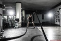 stock image of  Strong Men with battle rope battle ropes exercise in the fitness gym. CrossFit.