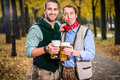 Men in bayrischer Tracht clinking glasses with beer