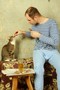 Men with a beer next to the cat steals fish Royalty Free Stock Photo