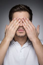 Men with closed eyes portrait of young men closing his eyes by man hands while standing on grey Royalty Free Stock Photos