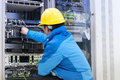 Men connect the network cable to the switch in the engine room Royalty Free Stock Photo