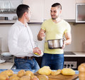 Men cooking potato soup mature father and adult son indoors focus on the right man Stock Photos